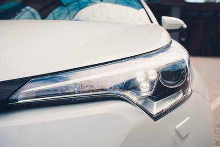 Led car headlight close-up. New modern vehicle detail of lamps light Фото со стока