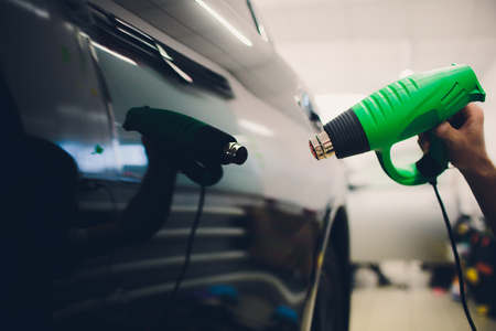 Master installs a tint film for the car with a hairdryer. Concept protection car Stock Photo