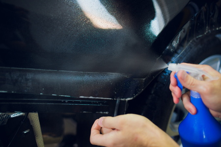 Worker hands installs car paint protection film wrap
