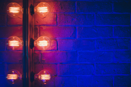 Decorative antique edison style light tungsten bulbs against brick wall background Stock Photo