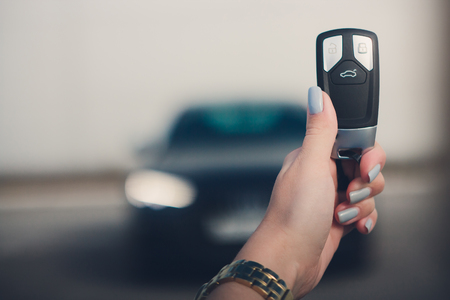 Close up hand of Man holding car key with blurred black car on background