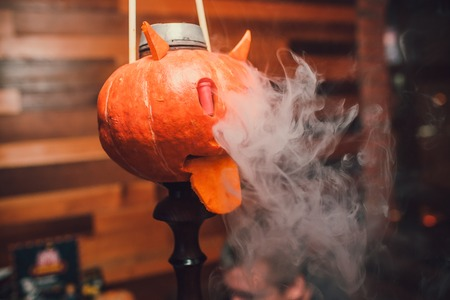 Hookah with smoke on the background of a brick wall with a pumpkin. Abstract Halloween background with pumpkin. Flashes of light, glare of light, an old empty room Stock Photo