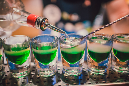 Green liquid in shot glasses standing on the counter bartender preparing shots