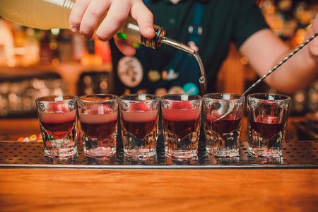 Il barista sta versando la tequila nel bicchiere sullo sfondo del bar