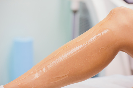 beauty, depilation, epilation, hair removal and people concept - beautiful woman with applicator applying depilatory wax to her leg. Stock Photo