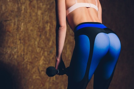 Sexy beautiful ass in thong. Fitness girl, athletic woman working out with dumbbells. Imagens