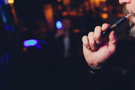 Eine hitzebeständige Tabakprodukttechnologie. Mann, der vor dem Rauchen in einer Hand das Rauchmodul hält.