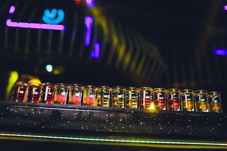 Variation of hard alcoholic shots served on bar counter. Blur bottles on background. Stock Photo