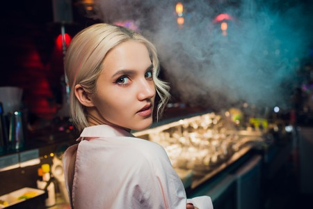 Portrait of a girl in a night bar, behind the counter.