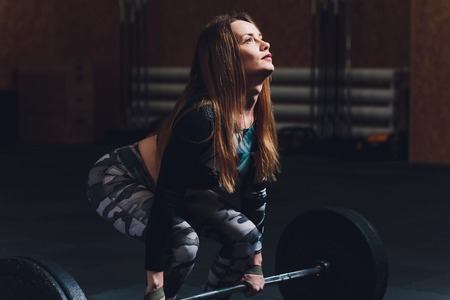Attractive young sports woman with barbell. Deadlift. Stock Photo