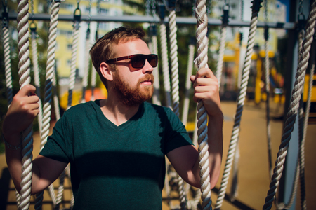 adult man in playground. man with beard and glasses. stylish modern young