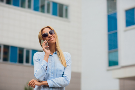 Portrait young businesswoman communicating on cell phone while leaning on glass wall Stock Photo