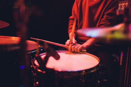 Human hands playing the drum with drumstick