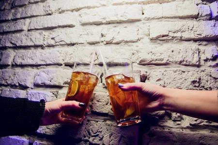 Dos hermosas mujeres divirtiéndose en un bar bebiendo cócteles.