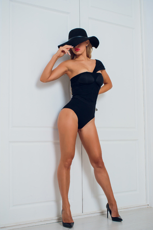 girl blonde on a white background in a black baud and hat. Archivio Fotografico