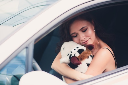 Young beauty woman and small soft toy in clothes in car.