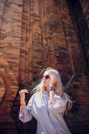 young girl in blue robe against background temple wall in sunglasses. CONCEPTION MODERN RELIGION