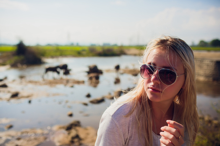 Beautiful blond young woman in green rice fields meadow