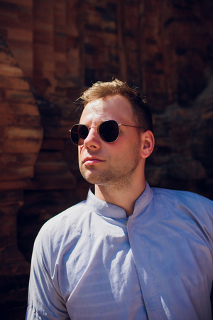 man in blue robe against background temple wall in sunglasses. CONCEPTION OF MODERN RELIGION