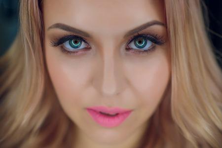 Maquillaje brillante de retrato de mujer de pelo rubio rizado. Foto de archivo