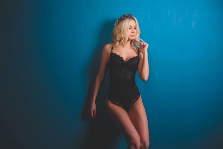 girl blonde on a blue background in a black baud and hat.