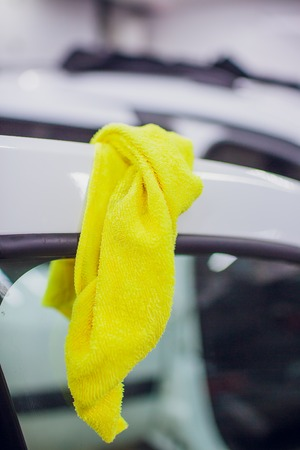 Man cleaning car door with rag, closeup