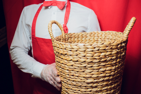 young handsome man holding basket in white and red uniform