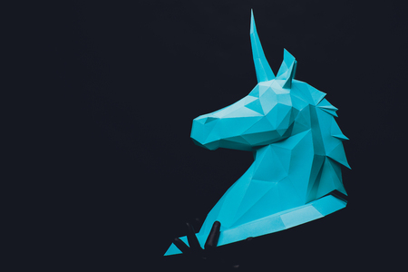 Unicorn head paper on black background. Hands in black gloves hold a turquoise Unicorn. Copy space