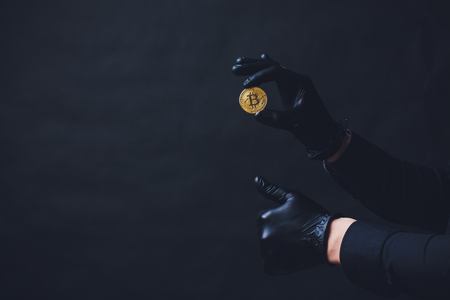 Bitcoins placed on arm Hands in black gloves show symbol. Isolated on black background Stock Photo