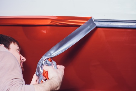 Car wrapping specialist putting vinyl foil or film on car. cutting protective film with torch. wrapping yacht, boat, ship, car, mobile home. orange film Stockfoto