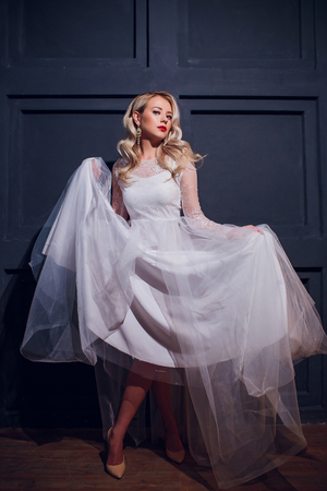 Fashion portrait Beautiful Young Woman with Blonde Hair. Girl in white Dress on White Background