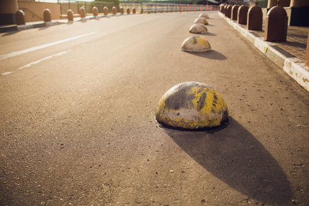 Iron balls aligned along a road border, in a french city. Abstract design with pattern of round shapes and a white line on the asphalt surface. Decorative delimitation of a sidewalk.