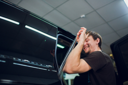 Worker hands installs car paint protection film wrap. holds a film in the style of a Turkish chef, the concept of humor