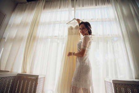 Pretty brunette bride in silk dressing gown and lacy veil holding wedding dress on a hanger near the window.