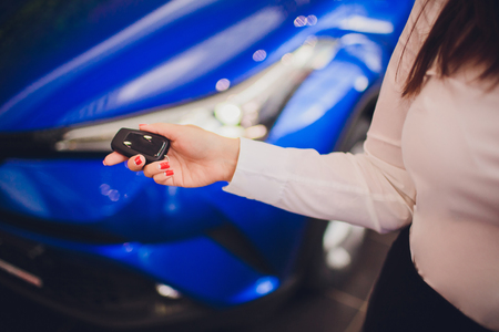 Female holding car keys with car on background