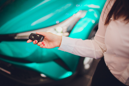 Female holding car keys with car on background beige color