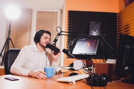 Portrait of radio host using sound mixer on table in studio. 写真素材
