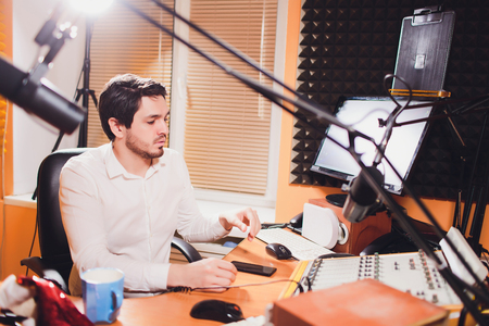 Portrait of handsome young latin man sitting in front of a microphone with laptop at radio station.