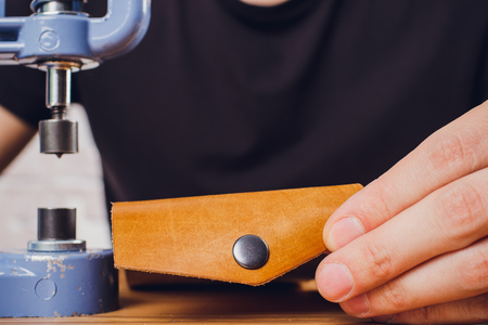leather craftsman working making products at table in workshop studio