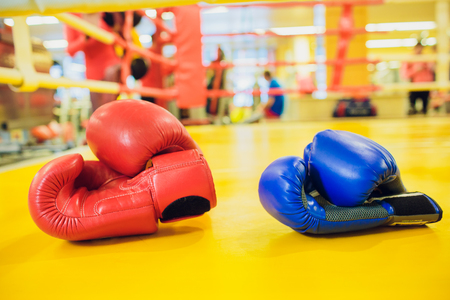 Red And Blue boxing gloves hanging on a Blue wall IN Gym Fitness yellow