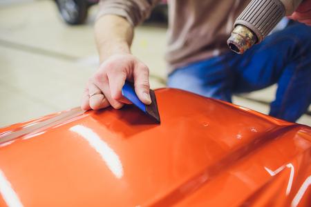Autoverpackungsspezialist, der Vinylfolie oder Film auf das Auto legt. Selektiver Fokus.