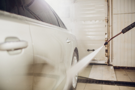 man washing automobile at manual car washing self service,cleaning with foam,pressured water.Transportation care concept.Washing car in self service station with high pressure blaster Banco de Imagens