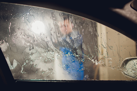 man washing automobile at manual car washing self service,cleaning with foam,pressured water.Transportation care concept.Washing car in self service station with high pressure blaster Stock Photo