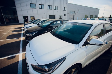 Car Sales and Loan Industry Concept. Row of Brand New Vehicles in Stock.