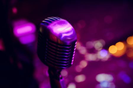 Micrófono en un escenario de stand up comedy con reflectores de rayos, imagen de alto contraste Foto de archivo