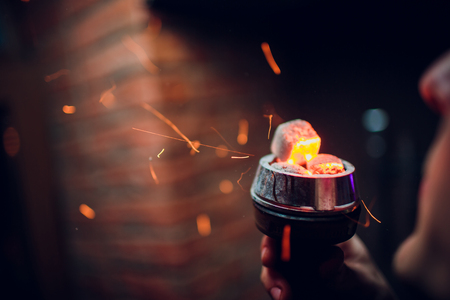 bowl of the hookah with red hot coals in the hands of a hookah on a dark background Smoking area Reklamní fotografie
