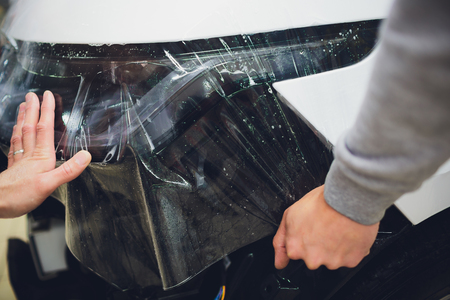 Transparent film, car paint protection, wrapping specialis. Car detailing Фото со стока