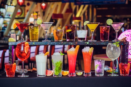 Various cocktails on dark background in cafe. Imagens