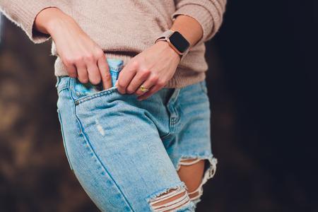 fille met de l'argent dans une poche de jeans en arrière des factures papier 200 et 2000 roubles
