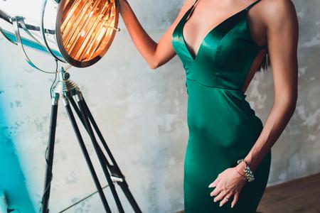 neckline, beautiful large female breast, green dress, close-up aluminum cinema spotlight